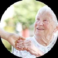 Frau hält Hand einer glücklichen Seniorin