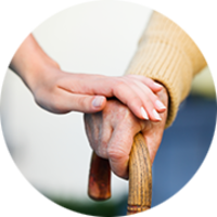 Frau hält Hand eines älteren Mannes mit Gehhilfe